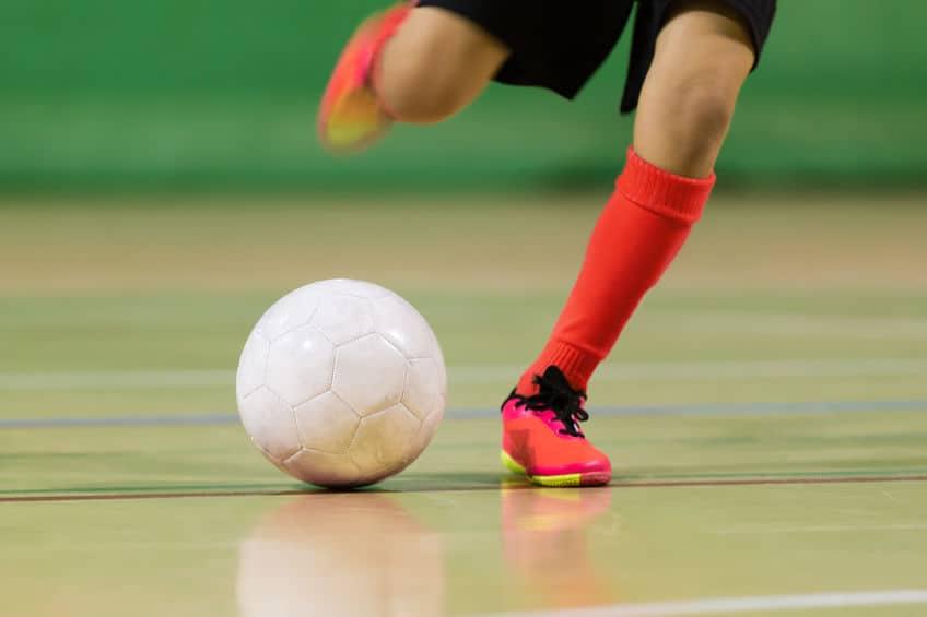 Imagem de pessoa jogando futsal em quadra.