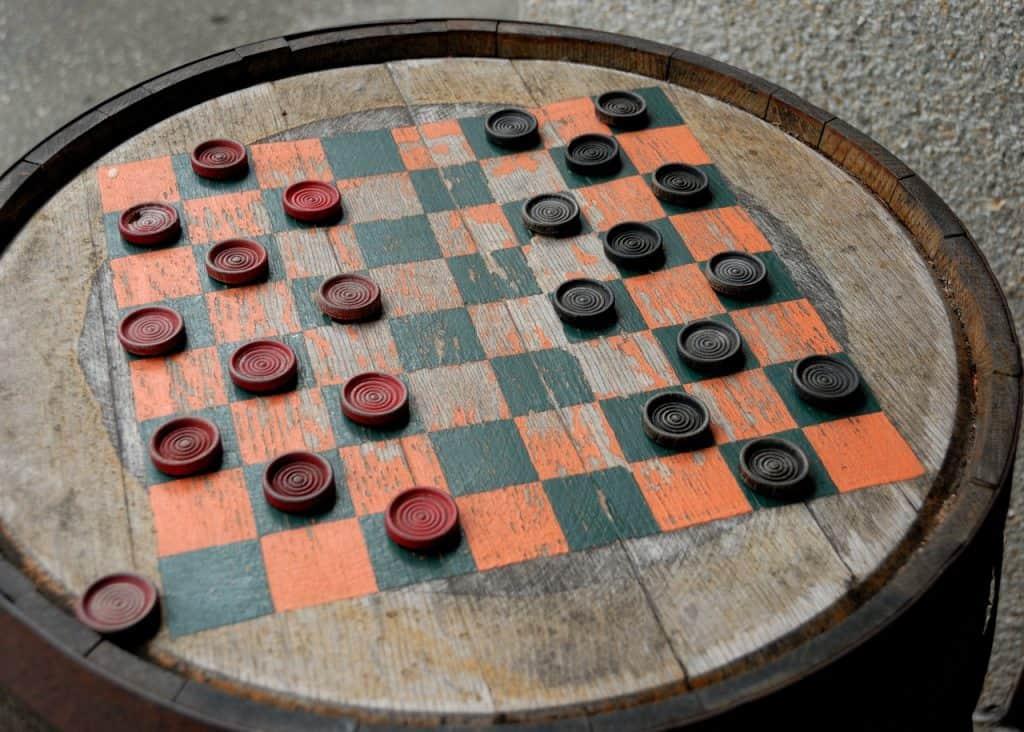 Imagem mostra um jogo de damas com peças pretas e vermelhas com o tabuleiro pintado na tampa de um barril.