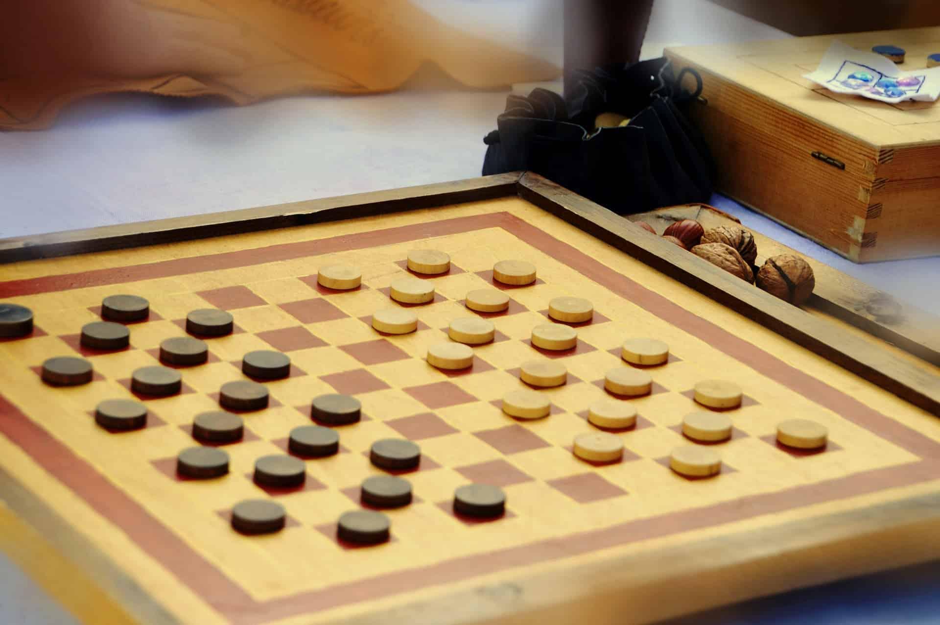 Imagem mostra um tabuleiro com peças de jogo de damas distribuídas.
