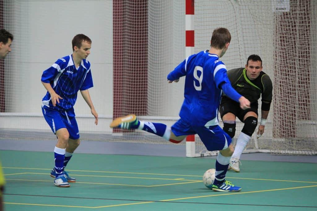 Imagem de homens jogando futebol em quadra.
