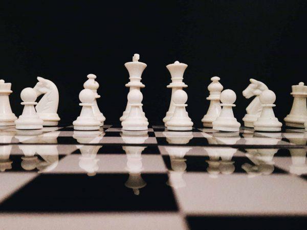 Imagem mostra o close do conjunto de peças brancas de um jogo de xadrez. Todas estão montadas sobre suas casas iniciais no tabuleiro.
