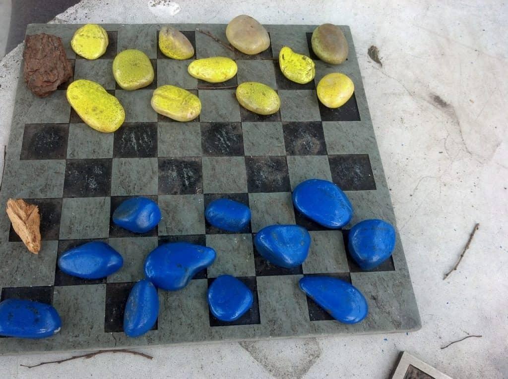 Imagem mostra um tabuleiro e pedras amarelas e azuis como peças do jogo de damas.