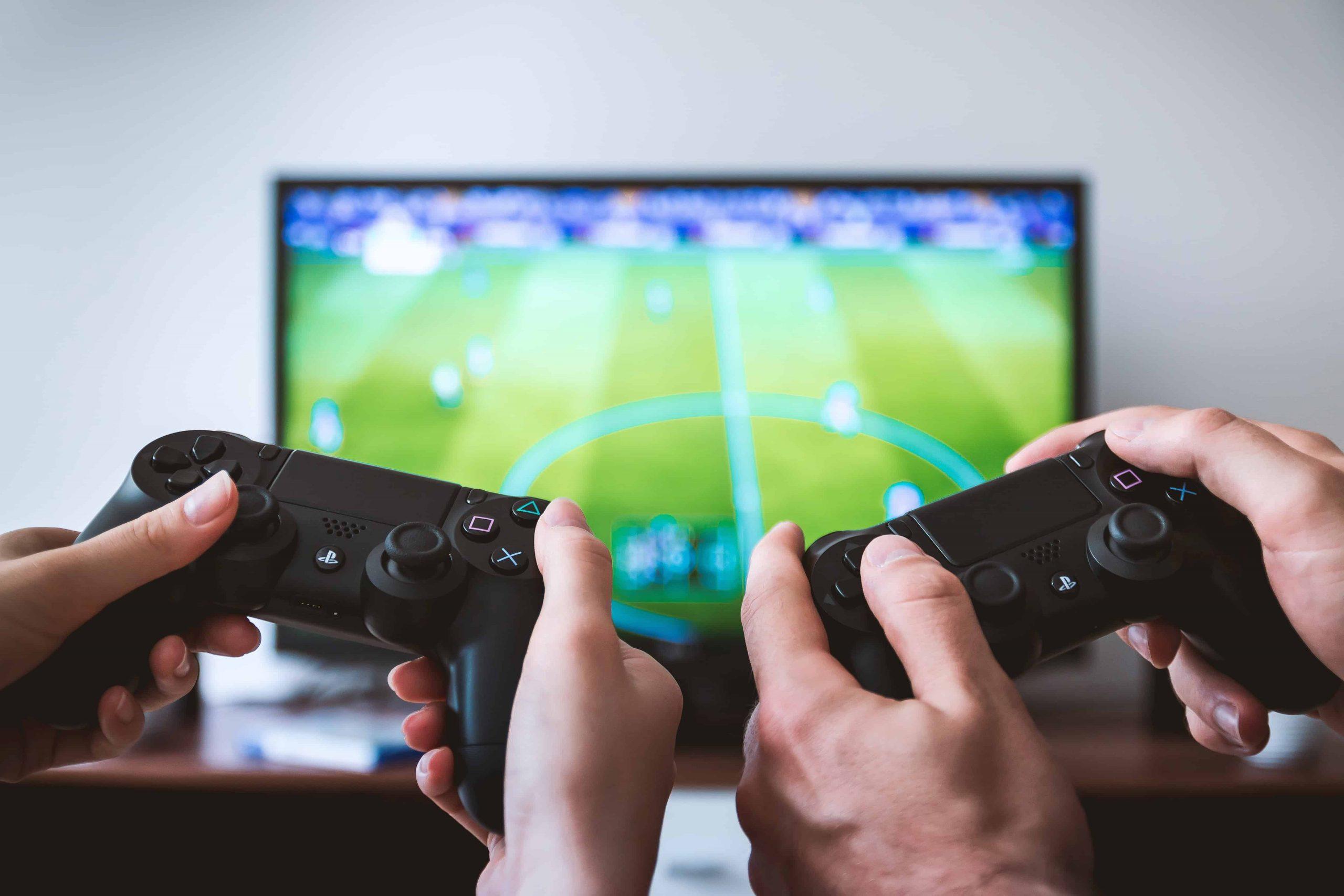 Imagem mostra uma televisão ao fundo e dois controles de Playstation erguidos segurados por duas pessoas.