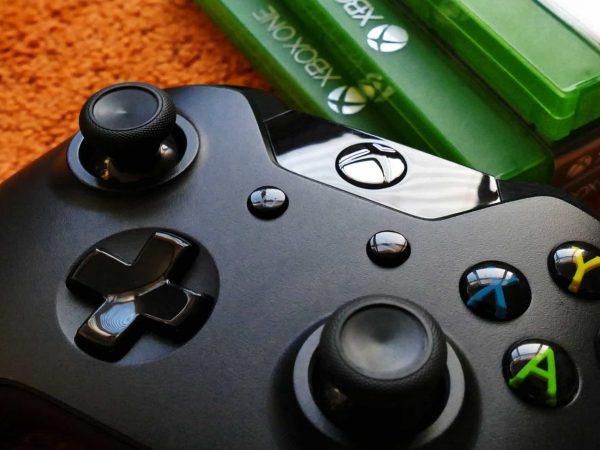 Imagem mostra um controle de Xbox de perto e algumas cases de jogos ao lado.