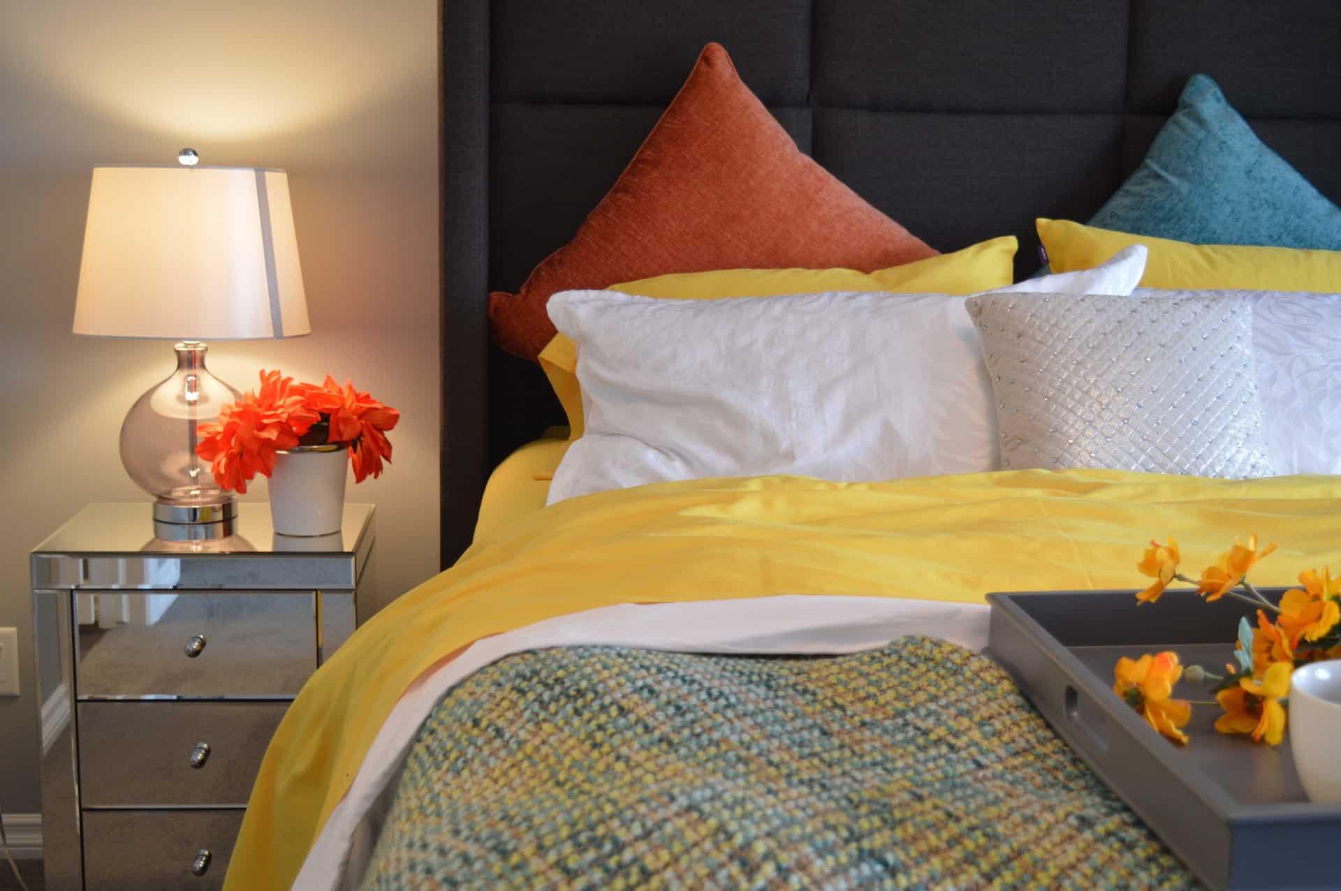 A imagem mostra parte de um quarto com detalhe no criado mudo e na cama. A cama está com um jogo de lençol amarelo e branco, uma colcha e travesseiros e almofadas coloridas.