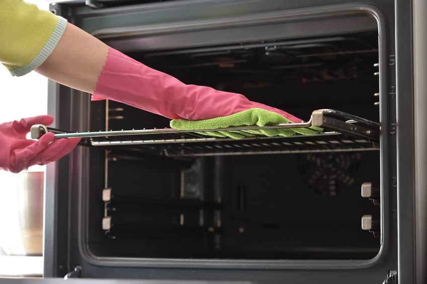 Imagem mostra mãos limpando a grade de um forno elétrico.