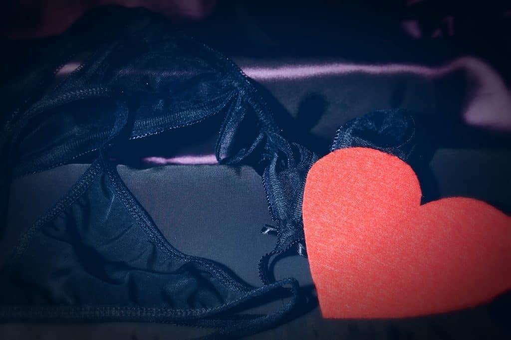 Imagem de jogo de lingerie sensual preta ao lado de coração de pelúcia vermelho.