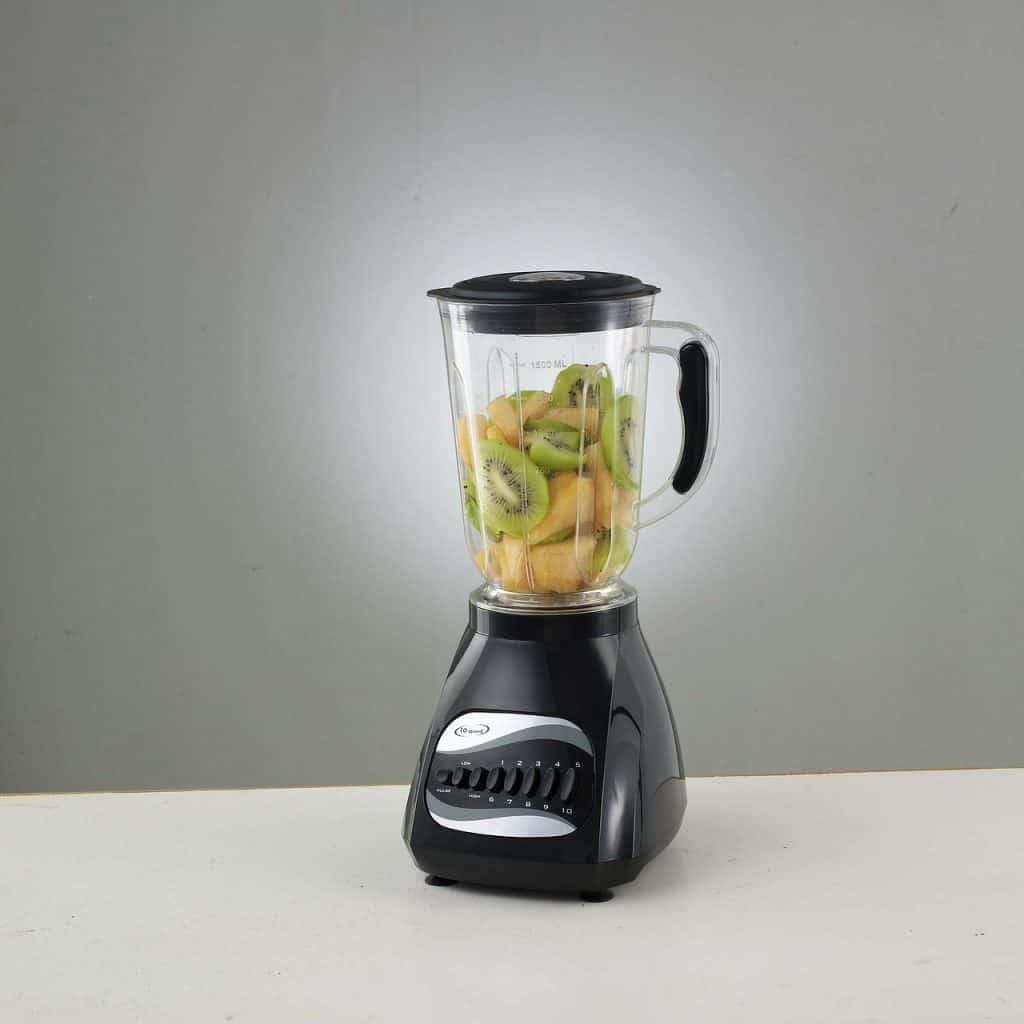 Imagem de um liquidificador com base preta e copo transparentes, com pedaços de frutas em seu interior.