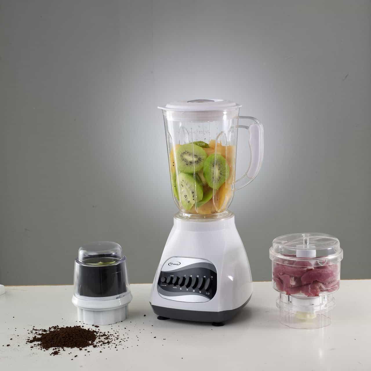 Imagem de um liquidificador com frutas em seu interior e dois recipientes com outros alimentos dentro.