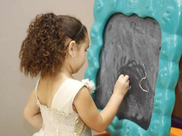 Imagem de menina desenhando com giz branco em lousa infantil com borda de plástico verde.