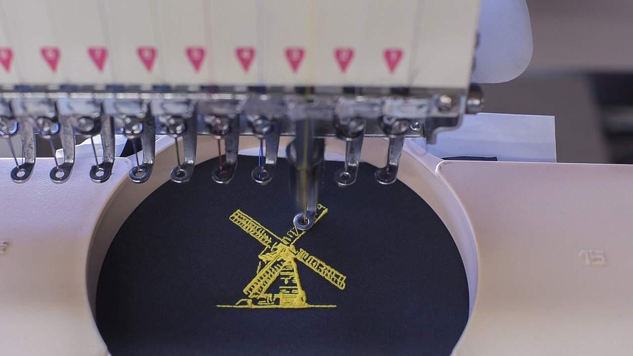 Na foto é possível ver as agulhas de uma máquina de costura bordando um moinho amarelo em tecido preto.