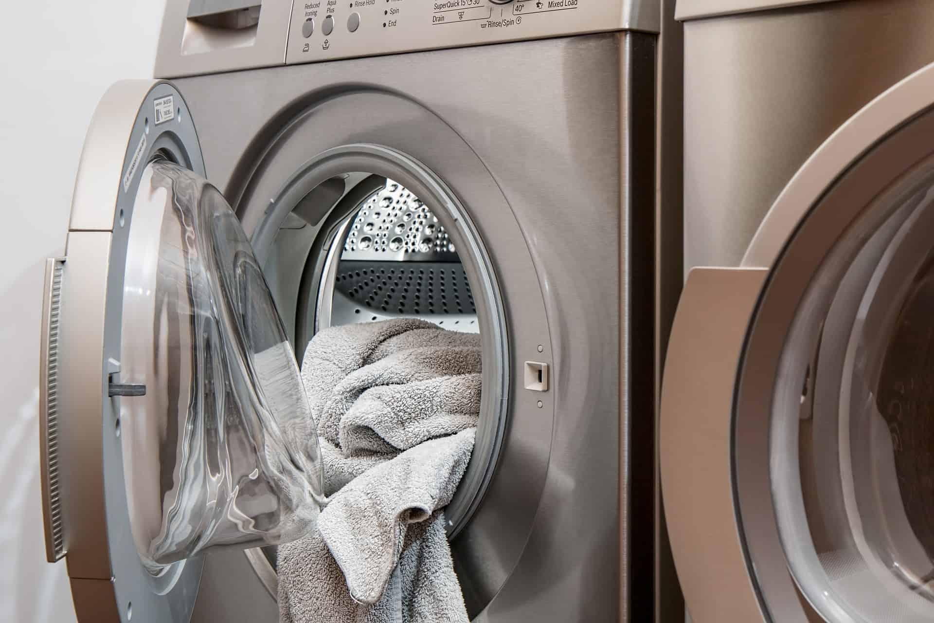 Máquina de lavar aberta com roupa dentro.