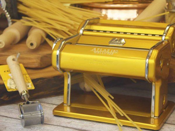 Imagem mostra máquina de macarrão na cor dourada com rolo e macarrão ao fundo.