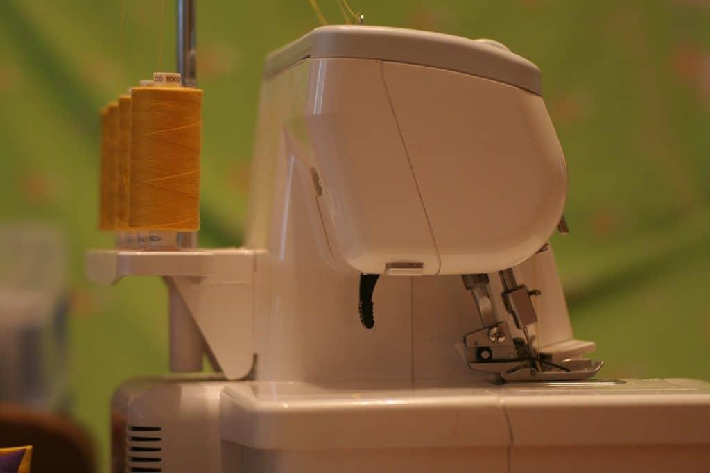 Na imagem está a lateral de uma máquina de bordar branca com linhas de cor mostarda atrás.