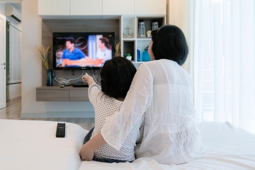 Mãe e filha sentadas no sofá da sala vendo tv que está no painel.
