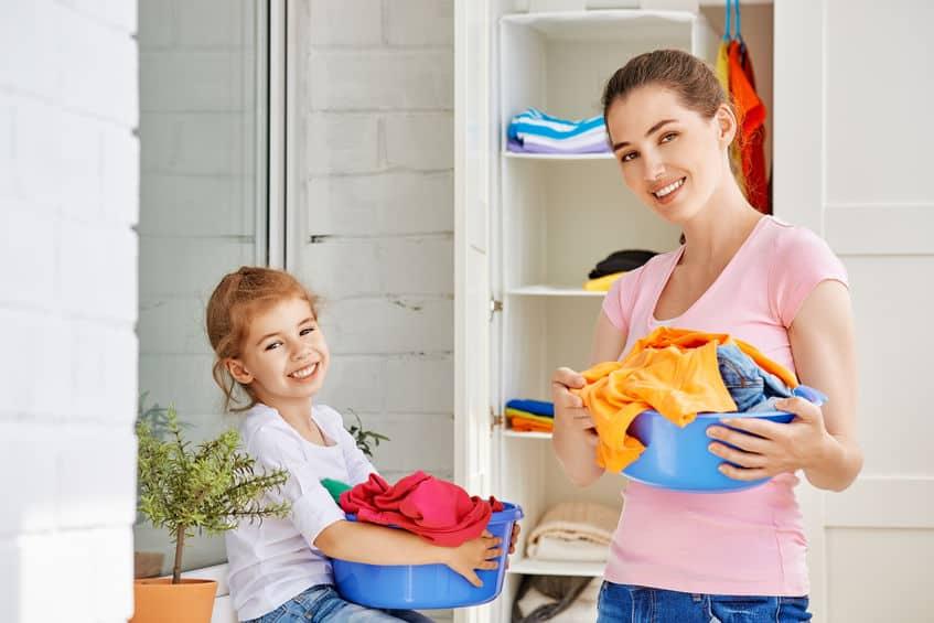 Mãe e filha na lavanderia organizando roupas.