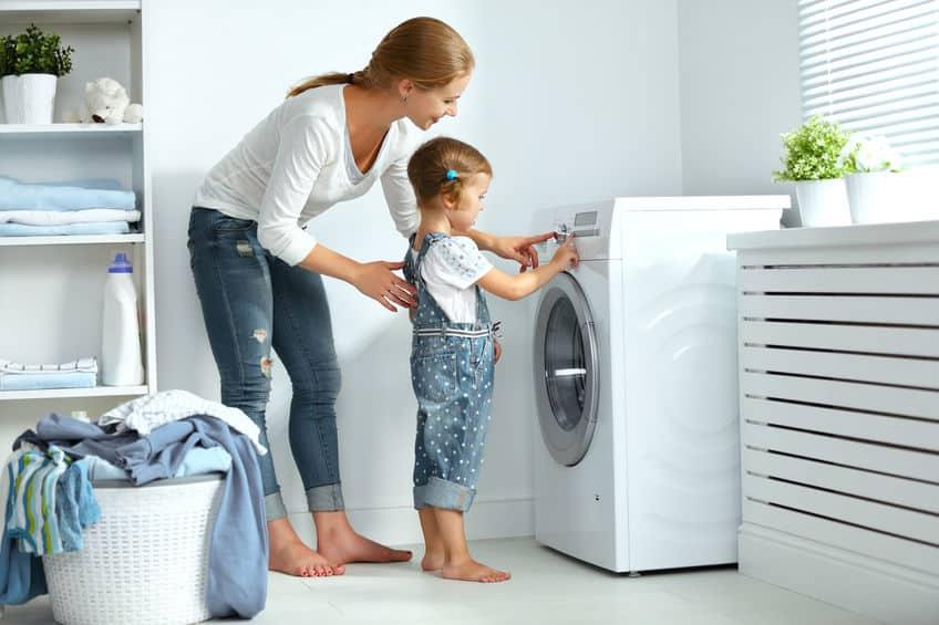 Imagem de mãe e filha em lavanderia, mexendo na máquina de lavar.