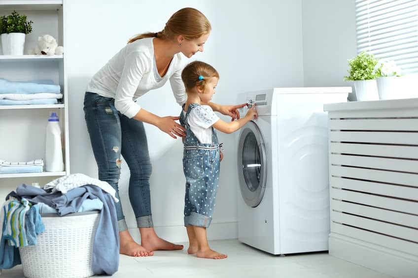 Imagem de mãe e filha em frente a maquina de lavar roupa.