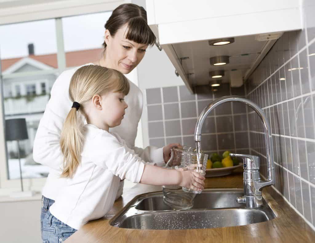 Imagem de mãe e filha na pia pegando água em torneira elétrica.