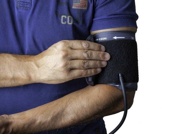 A imagem mostra close no tronco e braços de um homem. Em seu braço, há um manguito de medidor de pressão.