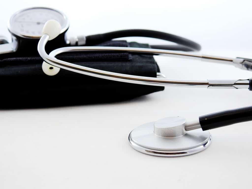 Medidor de pressão manual com manguito preto e estetoscópio.
