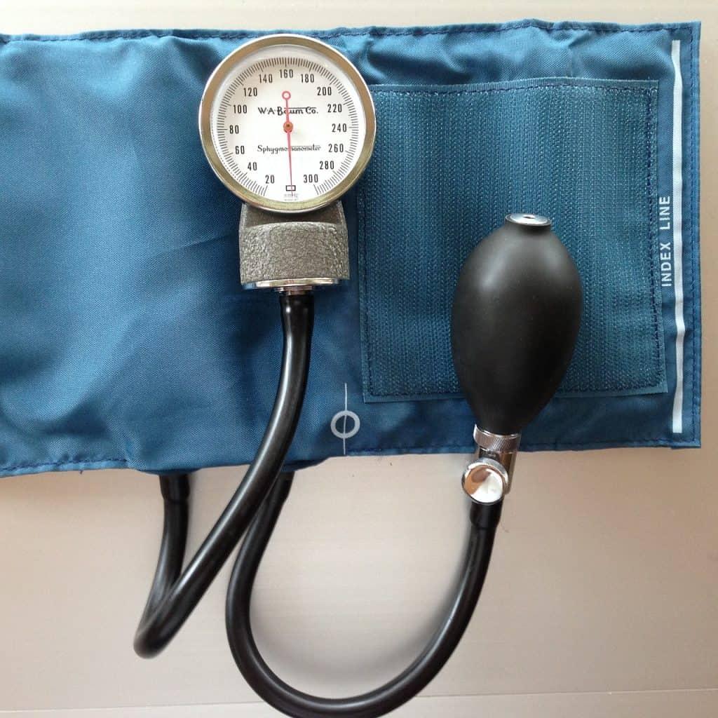 Imagem foca em um medidor de pressão manual com manguito azul escuro.
