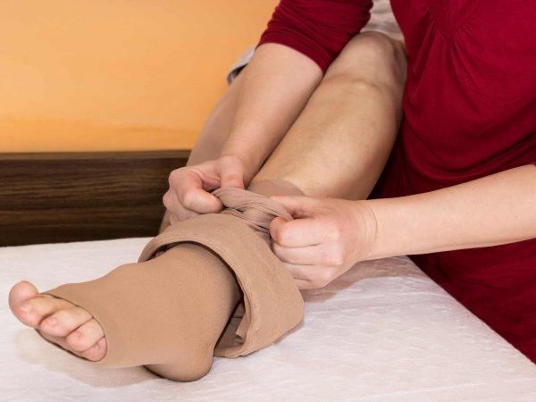 Imagem mostra pés de uma pessoa usando meia de compressão com abertura para os dedos.