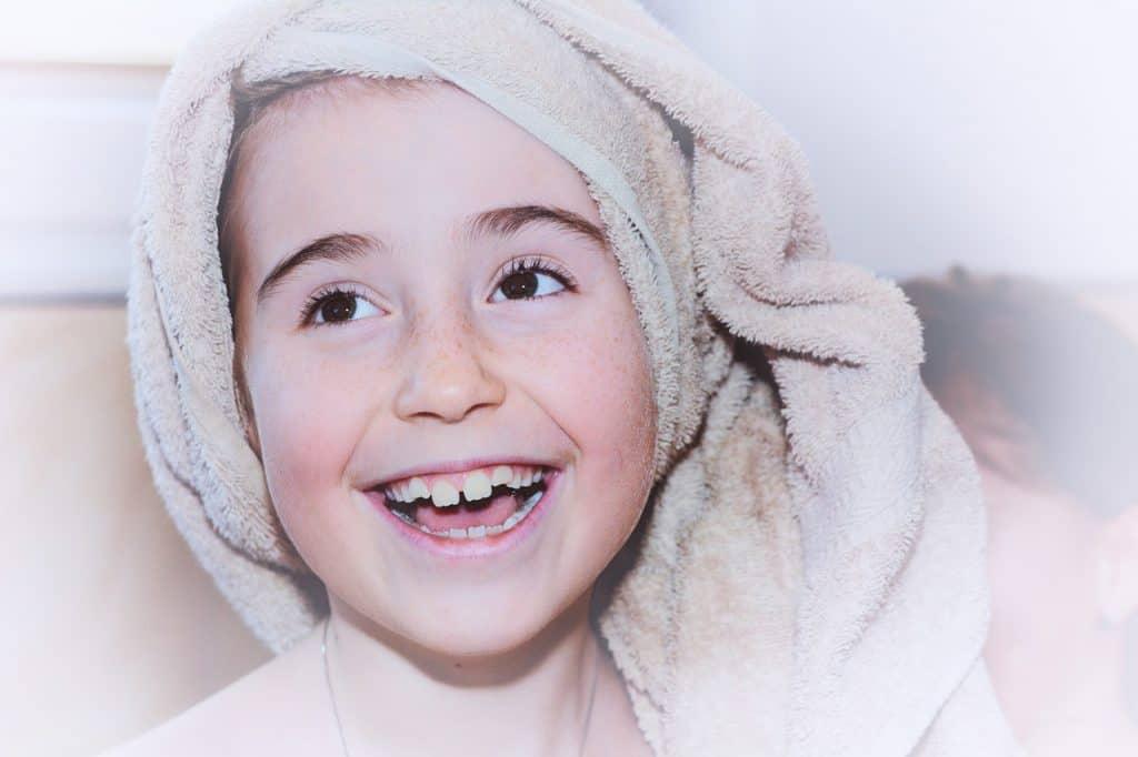 Em zoom, imagem mostra rosto de criança com toalha sobre os cabelos.