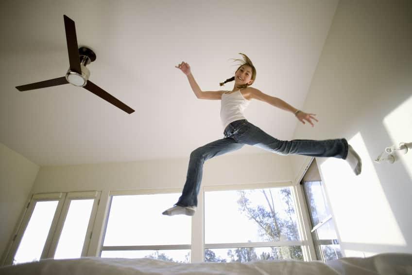 Imagem de menina pulando sobre cama com ventilador de teto ao lado.