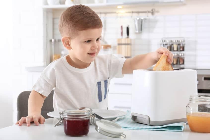 Menino retirando pão de uma torradeira no balcão da cozinha.