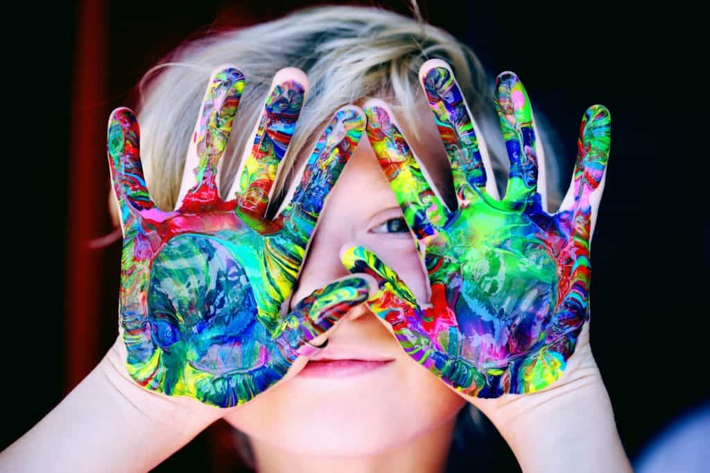 Na foto um menino louro com as mãos todas pintadas de tintas de diferentes cores.