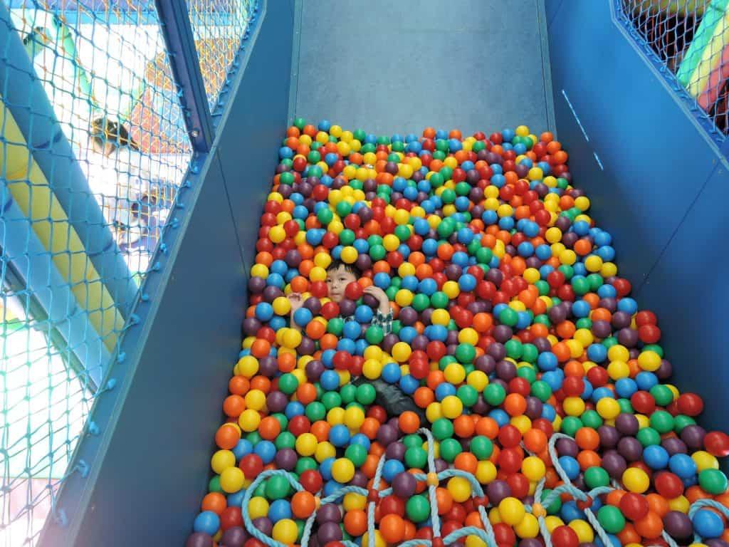 Imagem mostra uma criança coberta por bolas em uma piscina de bolinhas.