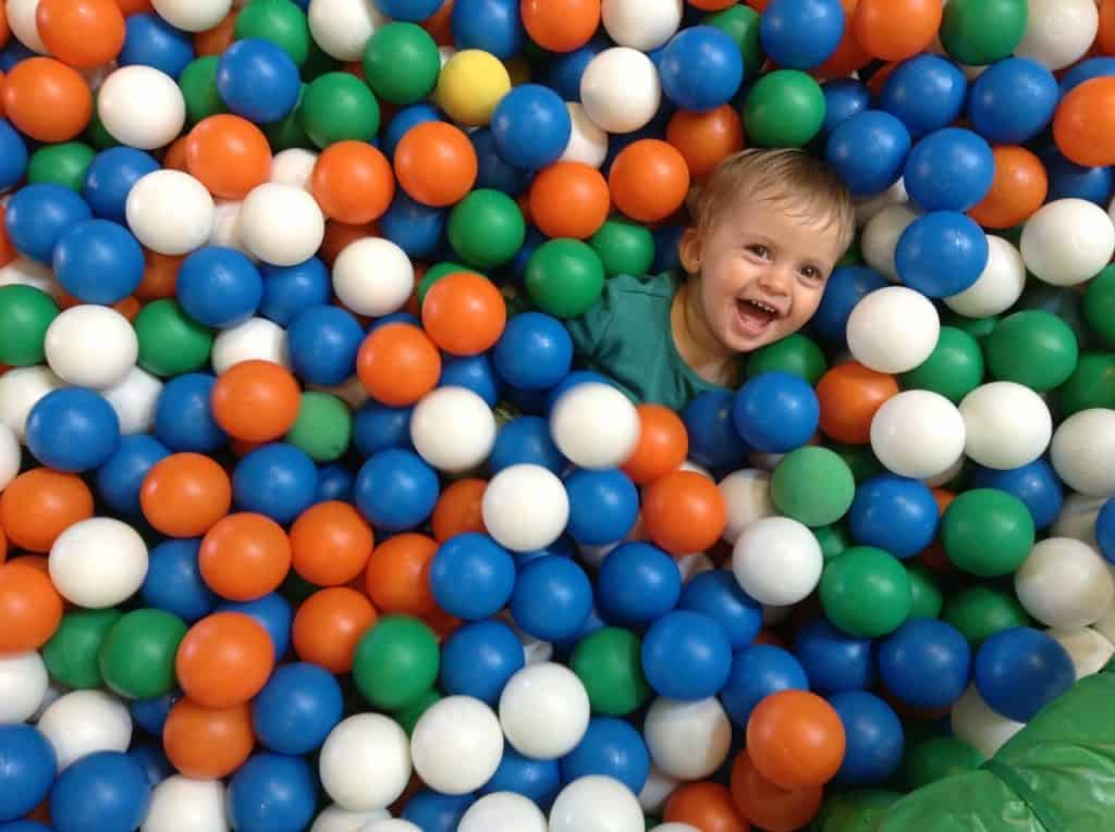 Imagem mostra um menino visto de cima feliz dentro de uma piscina de bolinhas.