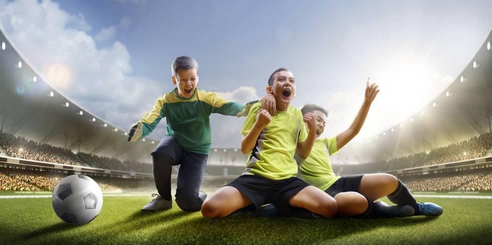 Três crianças comemorando um gol com um estádio ao fundo.