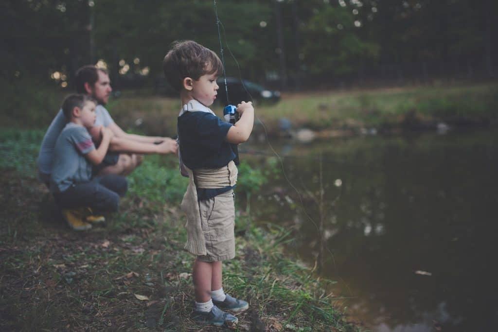 Imagem mostra um homem pescando com varas à beira de um lago junto com dois meninos.