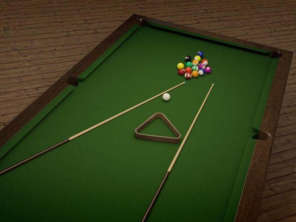 Imagem de dois tacos de sinuca e uma série de bolas sobre uma mesa de sinuca.