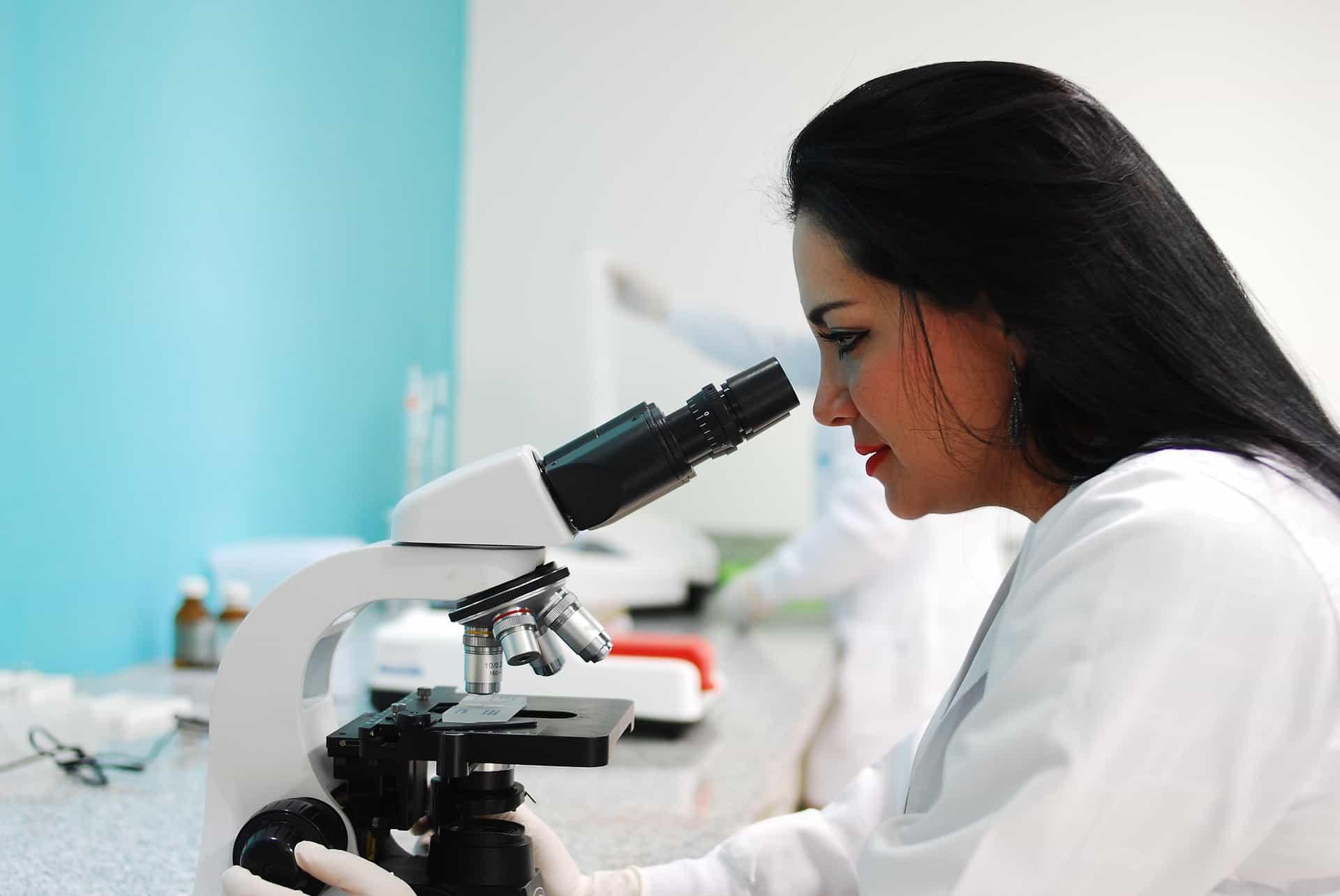 Foto de uma mulher observando uma amostra, por meio do microscópio.
