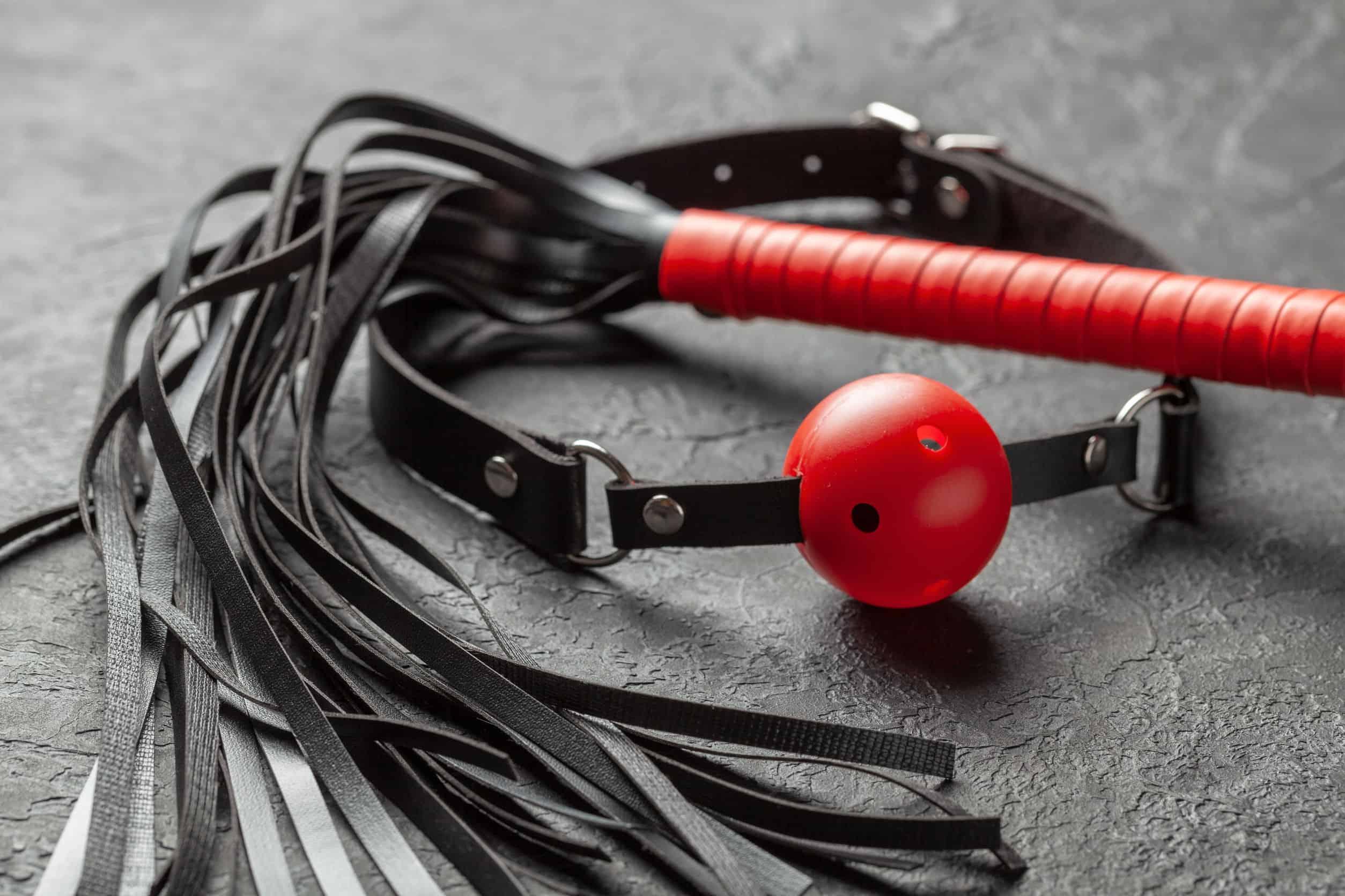 Imagem de mordaça com bola respirável vermelha e chicote de couro.
