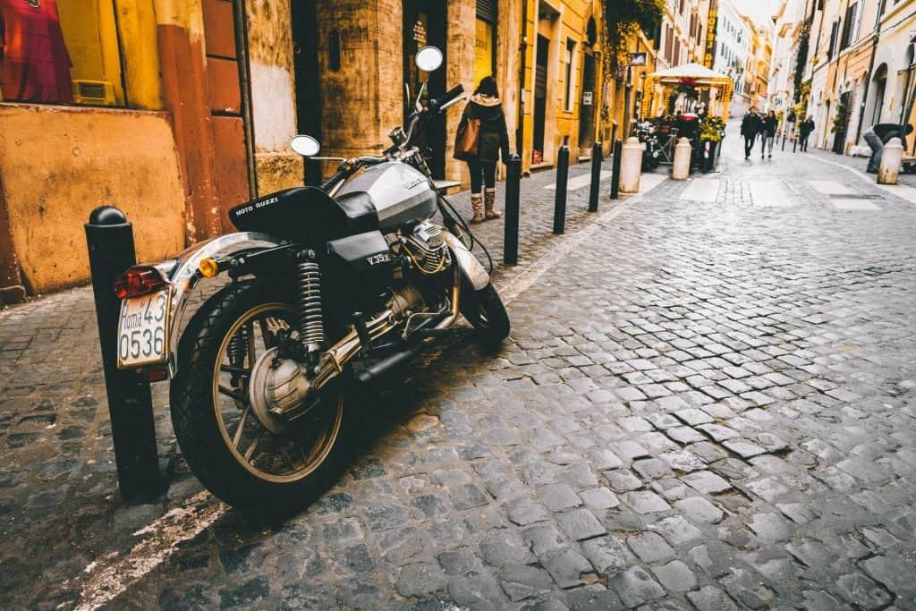 Imagem mostra mostra uma moto estacionada numa rua de paralelepípedos, ao lado de barras verticais de ferro.