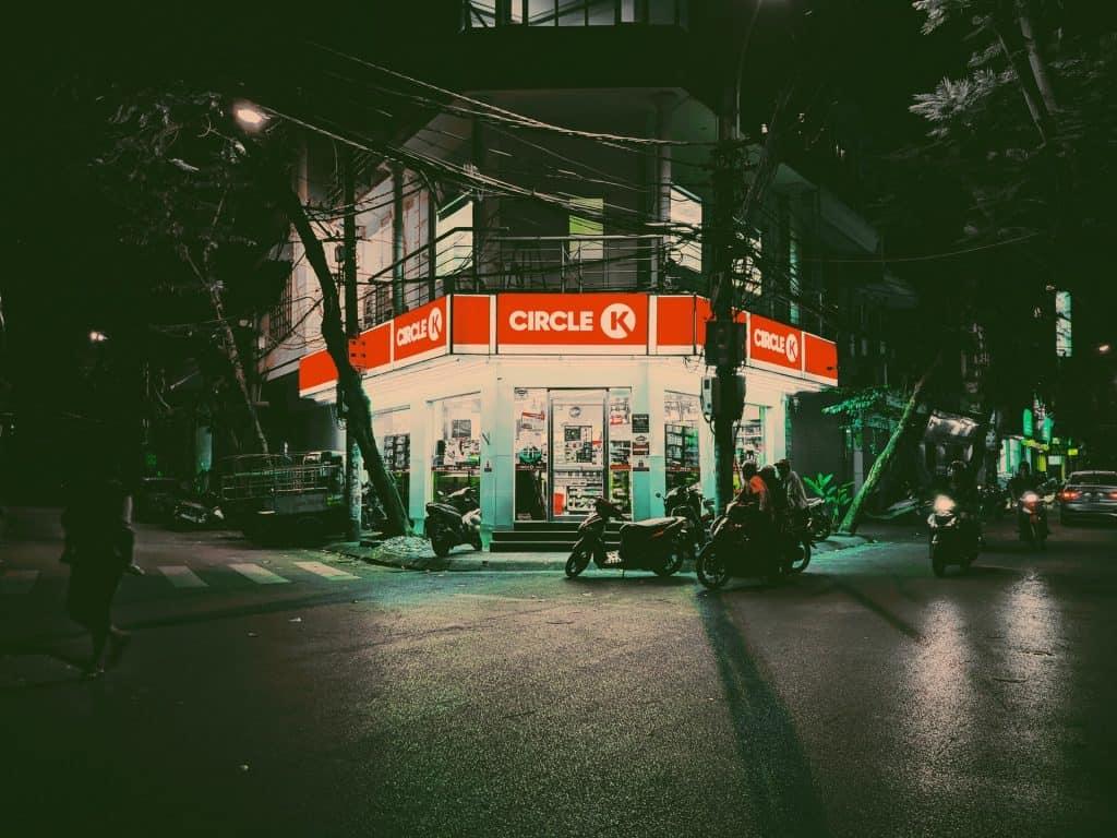Imagem mostra duas motos estacionadas em frente à uma loja, à noite, enquanto outras três motos se aproximam, pela direita.