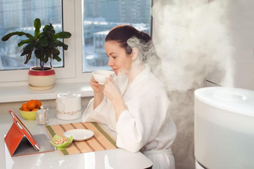Imagem de mulher lendo ao lado de umidificador de ar.