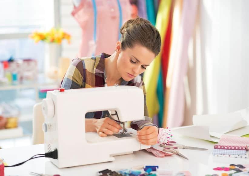 Imagem de mulher sentada e bordando com máquina de bordar.
