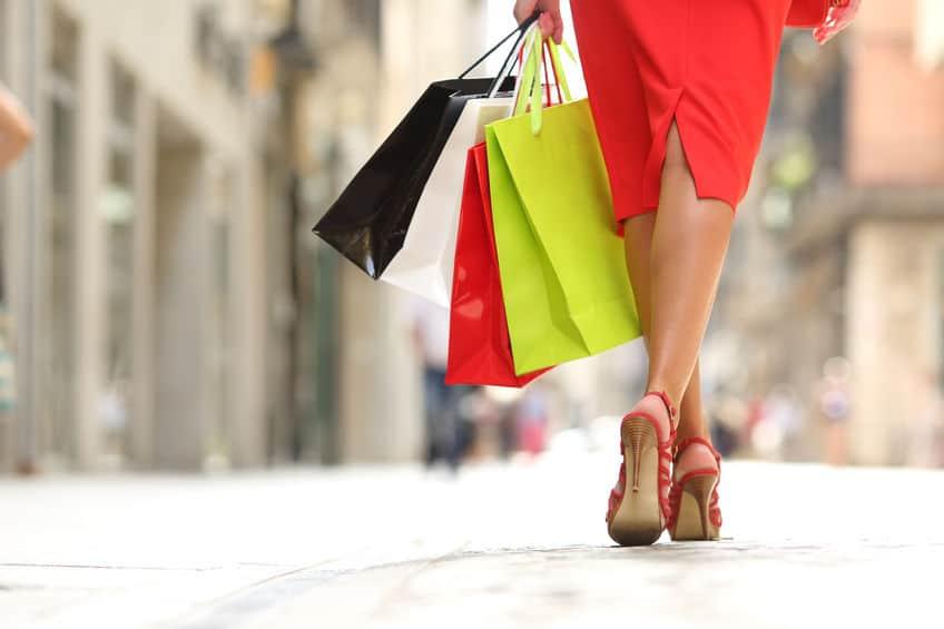 Close em pé de mulher de sandália de salto andando e carregando sacolas coloridas.