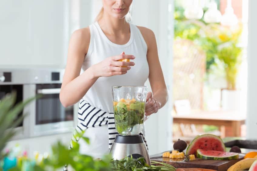 Mulher colocando frutas e verduras em liquidificador.