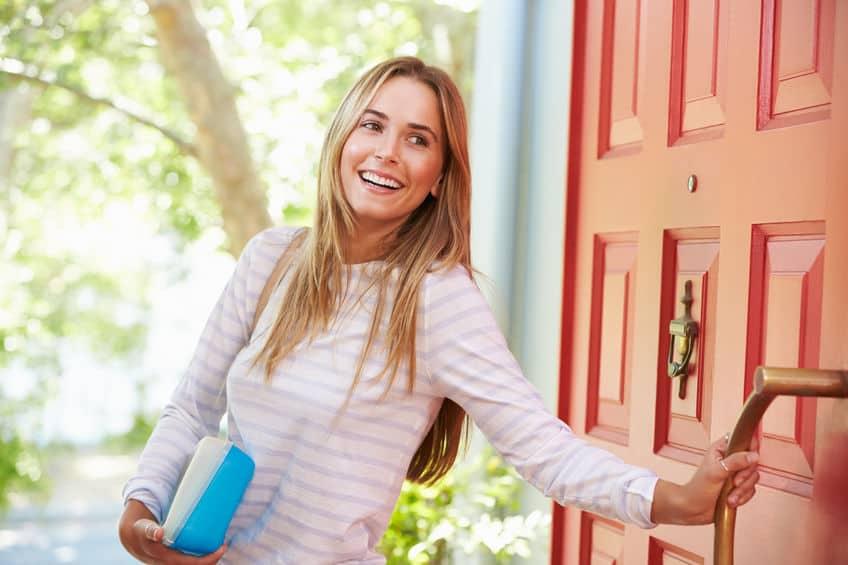 Mulher saindo de casa sorrindo com sua lancheira na mão.
