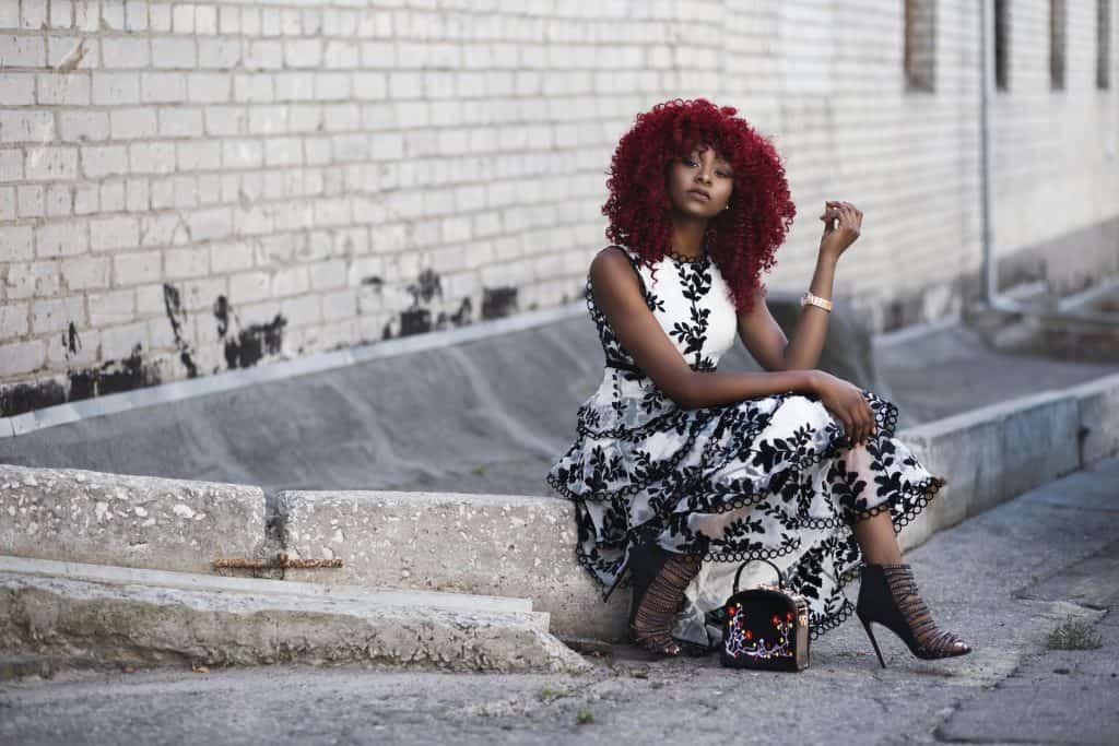 Imagem de mulher sentada em calçada usando sandália preta.