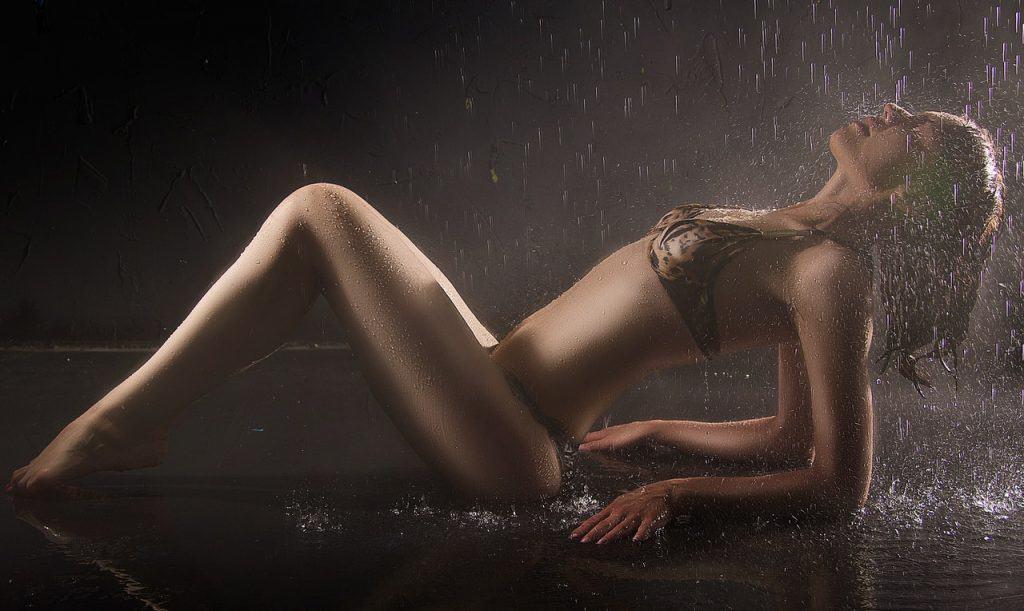 Imagem de mulher usando jogo de lingerie sensual com estampa de oncinha sob água caindo.