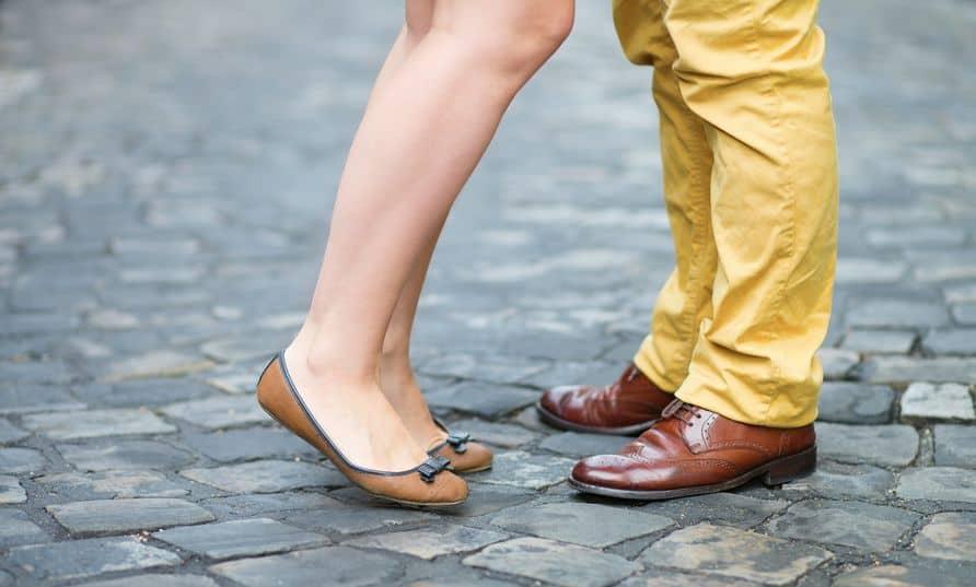 Pés de um casal, mulher veste sapatilha e home sapato.