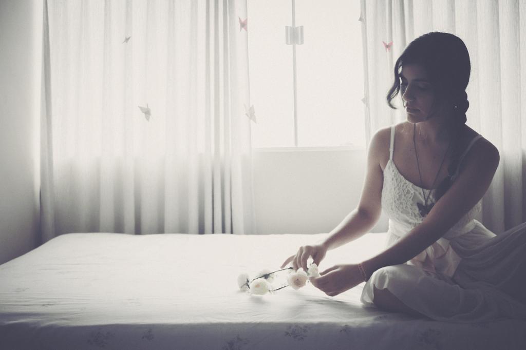 Imagem de mulher sentada em cama com lençol.