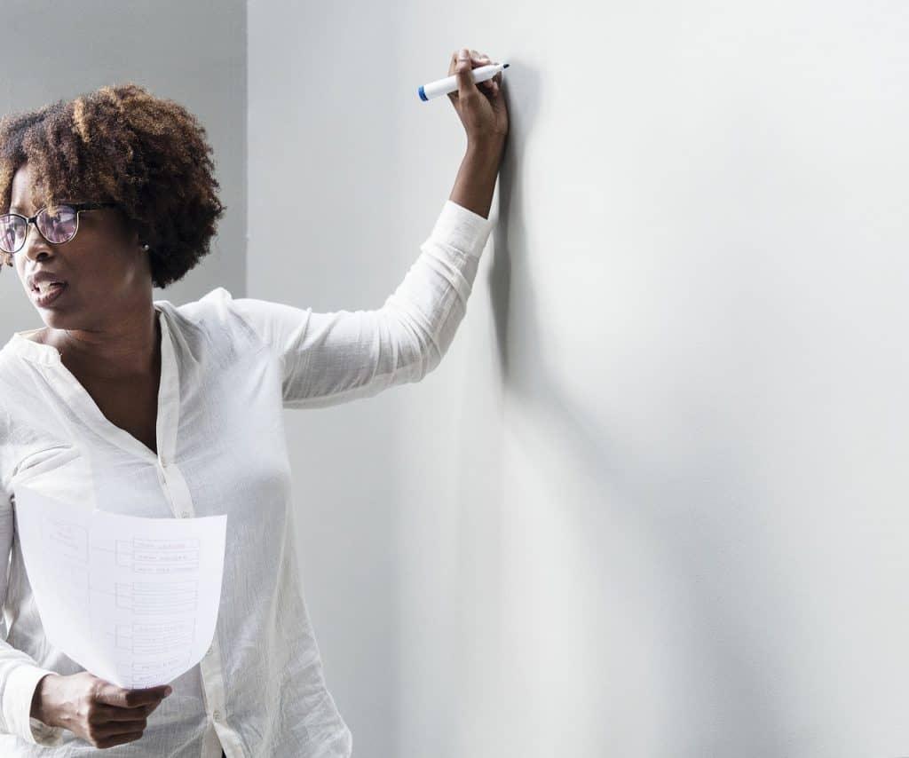 Imagem de mulher de negócios segurando um marcador azul para escrever em lousa branca.